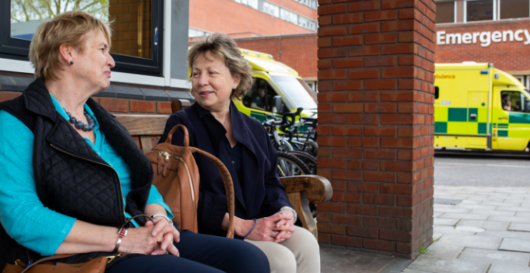 photo show two women sitting outside hospital emergency department