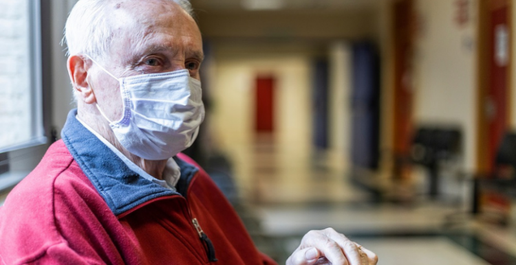 Older man wearing a face covering in hospital