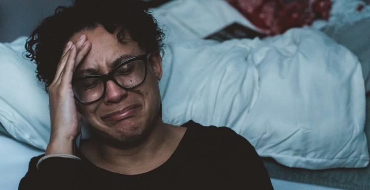 woman crying next to a bed