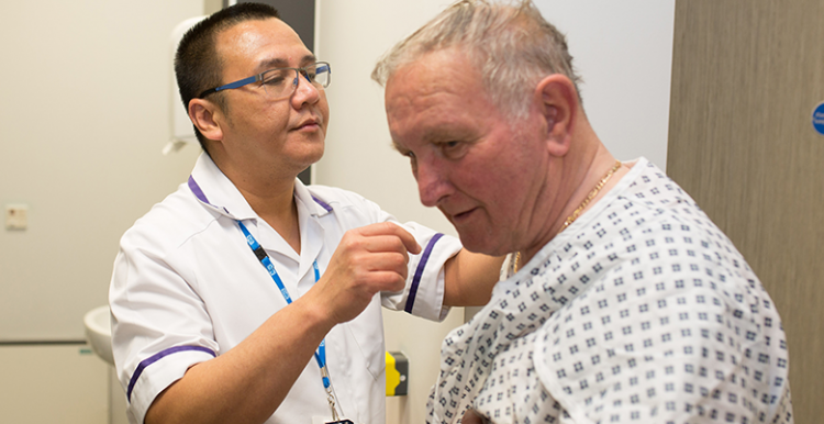 Picture shows man in hospital gown and an NHS radiographer preparing him for treatment