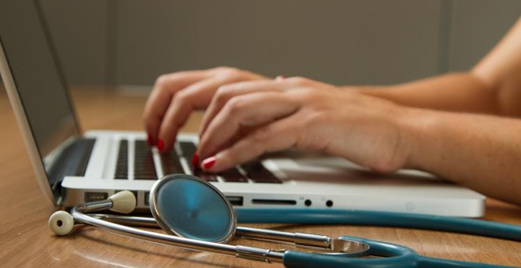 woman typing into laptop next to stethoscope