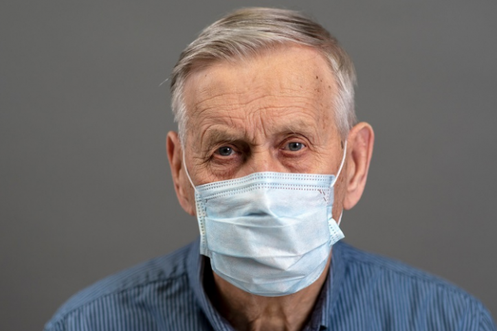 Older man in mask looking at camera