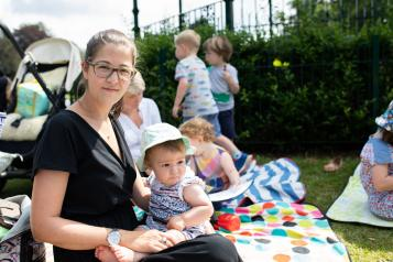Woman sitting on a picnic blanket with her baby