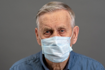 Older man in mask looking at camera