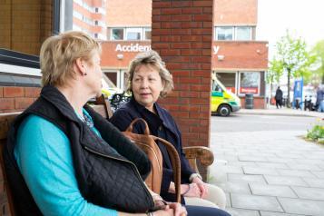 two women talking outside a hospital