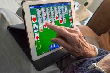 elderly lady playing game on tablet