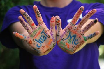 Picture shows words and designs painted on young person's hand