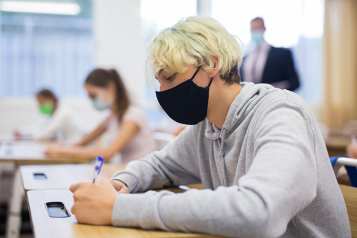 Picture shows young people wearing face coverings in classroom setting