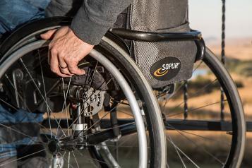 man's hand on a wheelchair wheel