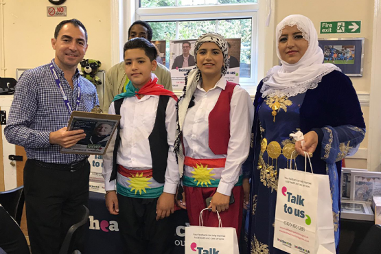 Picture shows Healthwatch staff member at an event in Peterborough with three members of the public and Healthwatch volunteer Patrick