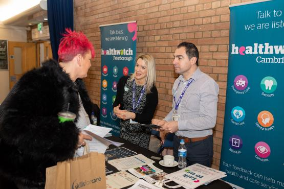 Healthwatch staff talking to people at an event