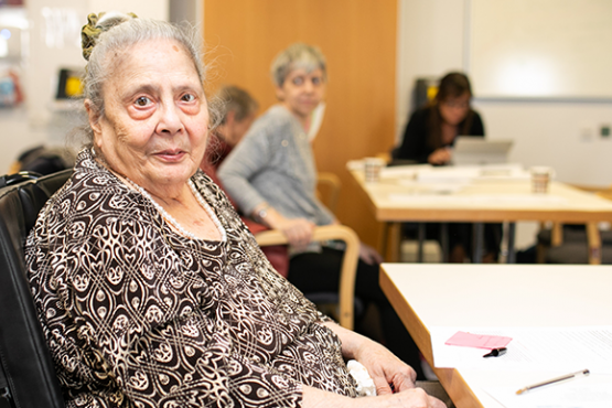 older woman sat in chair looking at camera