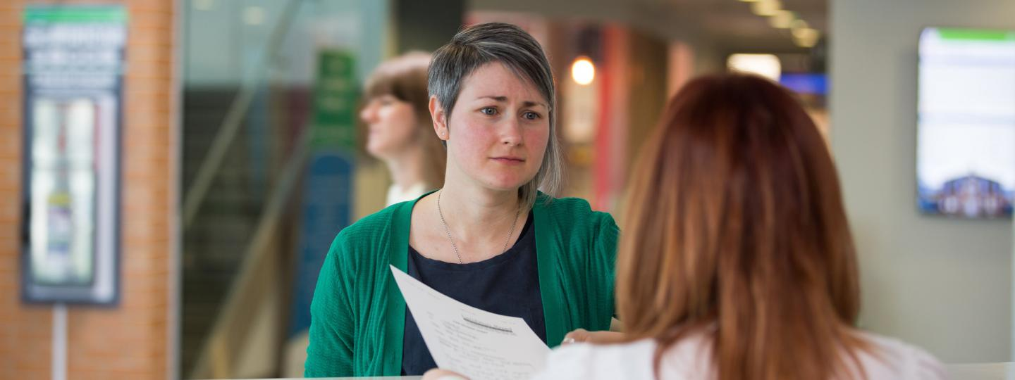 Woman at reception desk trying to complain