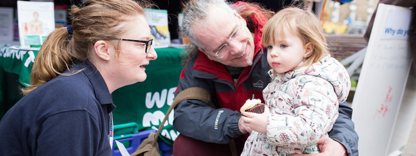 Healthwatch team talking to man with little girl