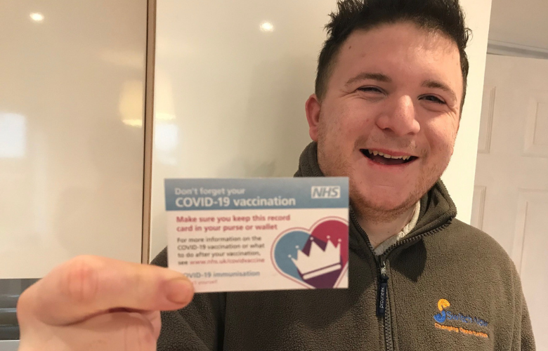 young man holding Covid-19 vaccination card