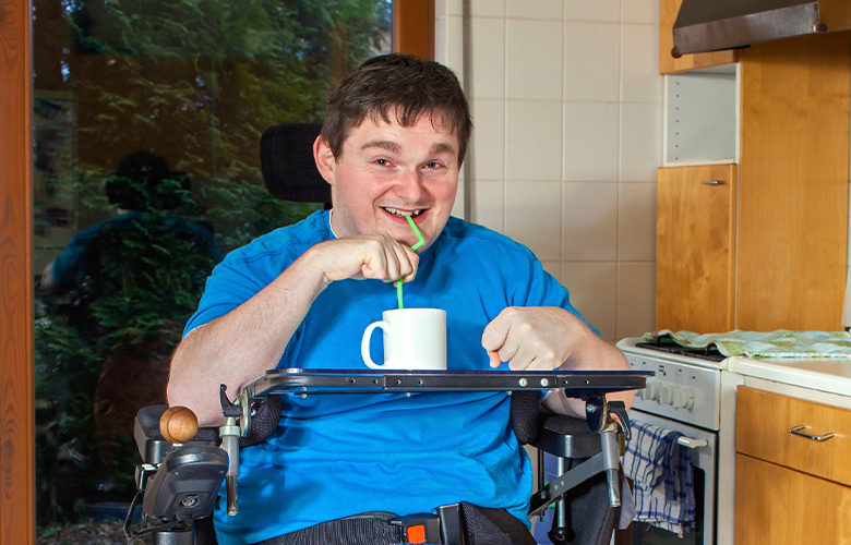 Picture shows man in wheelchair in his kitchen having a drink using a straw